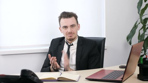 Young businessman in suit sitting in office and applauding, sarcasm, contempt 60 fps