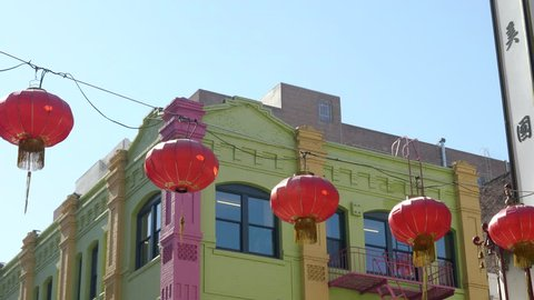red lanterns in front of a brightly painted building in chinatown of san francisco, usa