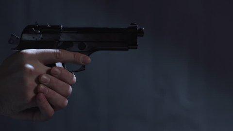 Close profile of man holding a 9 mm handgun takes three shots