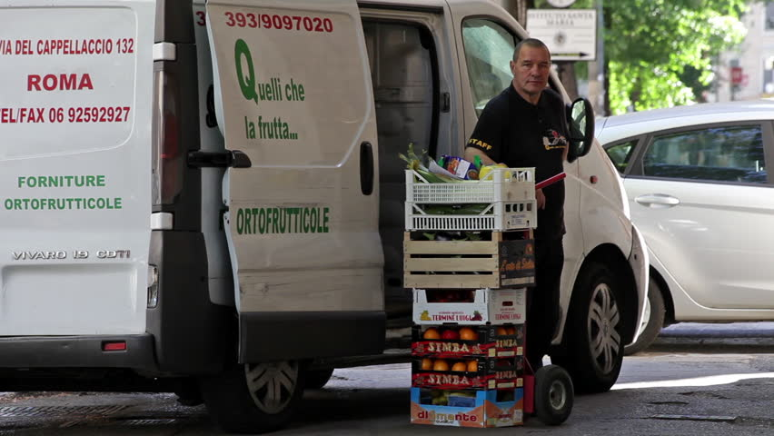 ROME - CIRCA MAY 2012 A delivery man stands next to his delivery van and a stack