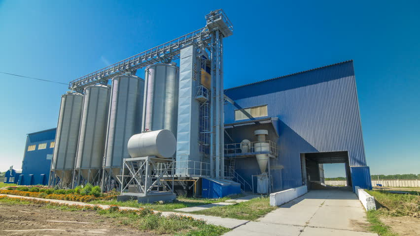 Modern large granary timelapse hyperlapse. Large metal silos. Elevator and factory. Sunny day, the blue sky.