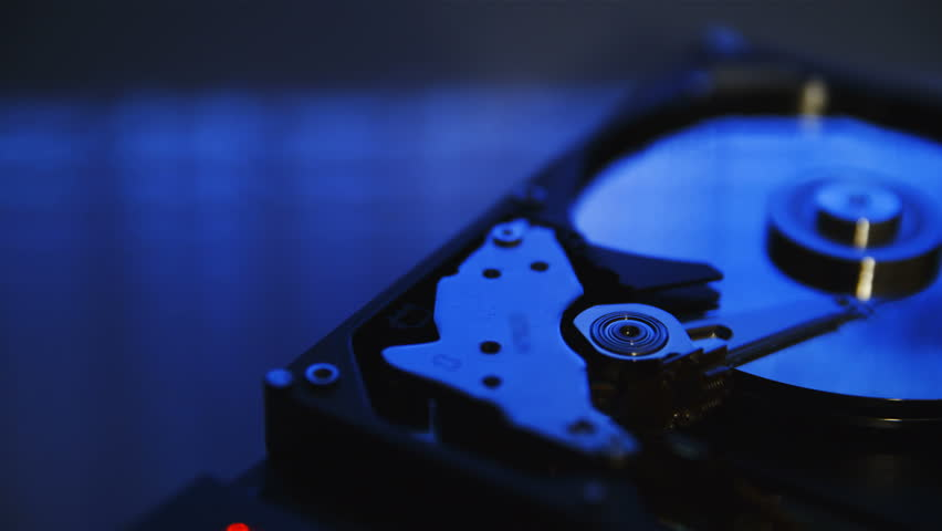 Hard disk drive read code from magnetic platters in slow motion 4K. Dolly slide of opened HDD in focus on a table in dark room. Reflection of blurred code reading.