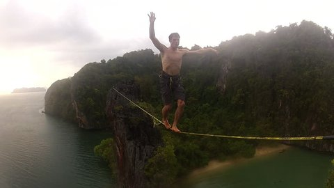 A brave and adventurous climber walks across a slackline over a bay in a tropical setting, with the ocean and jungle behind him, during the day