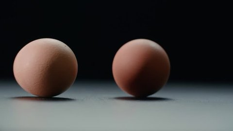 two chicken eggs spinning on a table in slow motion on a black background