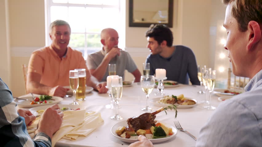 Men are eating at a dinner party. One man passes his plate for someone to put a piece of food on it.    Shutterstock HD Video #34757821