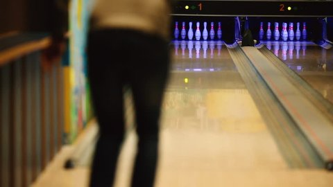 In the game club for bowling, the player throws a bowling ball that knocks down skittles. The focus on the pins, the player is blurred.