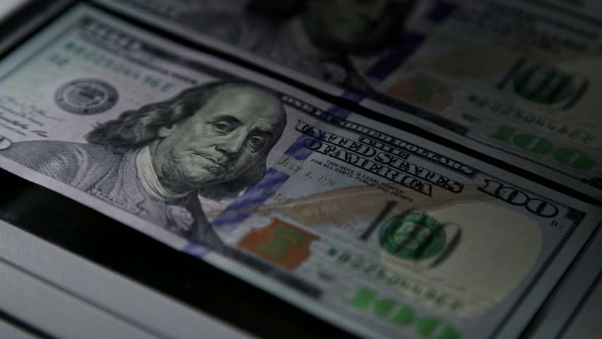 Money bills are checked for authenticity and shine through special green light. Fake and real money: check of bills in 100 dollars. Money and coins: ultraviolet shines through banknotes of 100  | Shutterstock HD Video #34765171