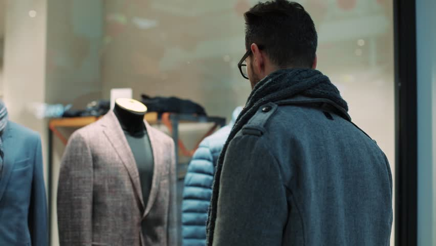 Portrait attractive man looking at shop window with men's suits in the mall christmas lifestyle building standing design money christmas tree shop store shopaholic storefront slow motion