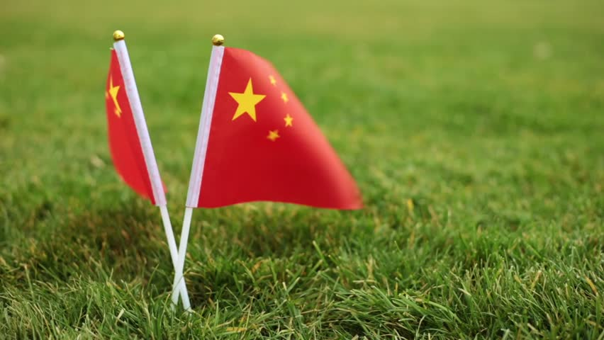 Chinese flag and soccer ball. Flag of China and football ball on the grass.