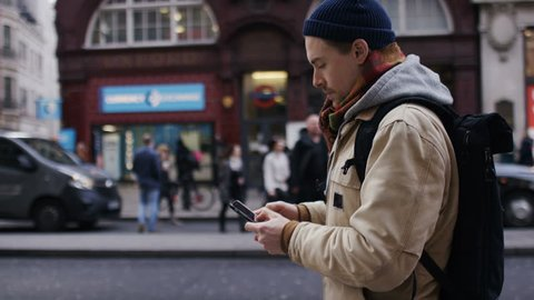 Young man using his phone as he walks on the high street, in slow motion