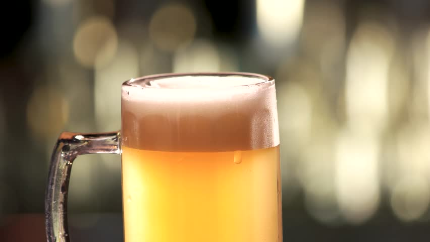 Close up slowly rotating glass of beer. Bartender stirring beer with spoon.   Shutterstock HD Video #34841521