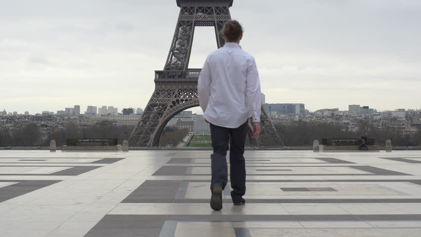 Young man walking towards Eiffel tower in Paris with suit on  | Shutterstock HD Video #34841644