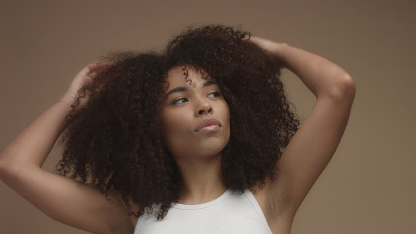Closeup portrait of mixed race black woman shaked head and her curly hair flying in air slowly. Touching it | Shutterstock HD Video #34852441