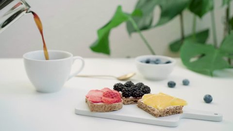 Table with pouring morning coffee with fruit sandwiches and blueberries. Healthy food breakfast concept. Tropical monstera plant on background.
