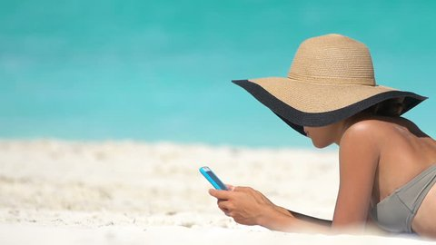 Woman using phone app on beach on summer travel vacation sunbathing on sand. Young female on smartphone lying on beach towel wearing sunhat by sea. She is wearing bikini while relaxing during summer.