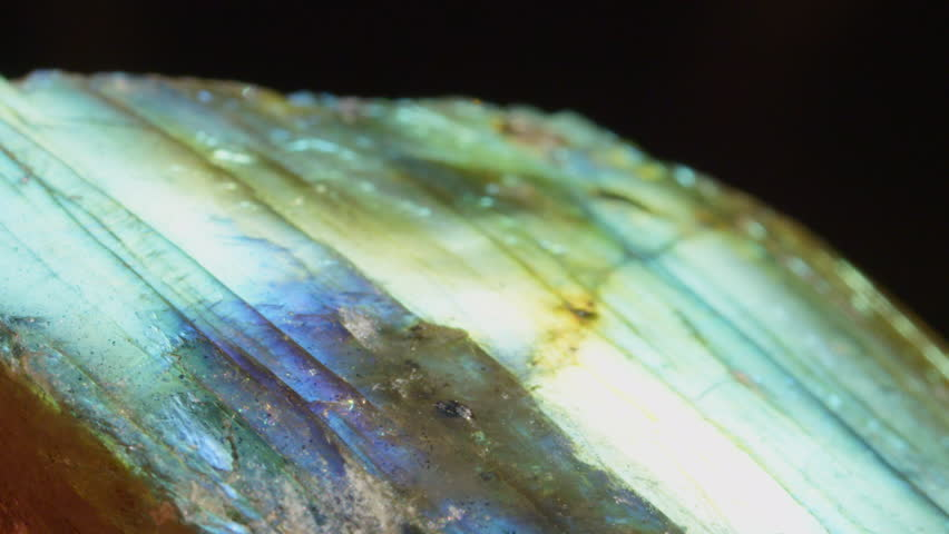MACRO: Mesmerizing iridescent tecosilicate mineral sparkling under light. Glowing feldspar revealing its multicolor structure. Labradorite crystal with healing properties igniting spiritual expansion