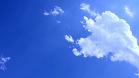 Time lapse clip of white fluffy clouds over blue sky, White clouds running over blue sky, Beautiful white clouds soar across the screen in time lapse fashion over a deep blue background.
