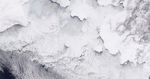 Very high-altitude overflight aerial of ice sheets and sea ice, northern Bering Sea coast. Clip loops and is reversible. Elements of this image furnished by NASA