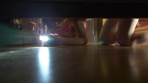 4k, slow motion, view from under the bed. A woman with a flashlight is looking for something under the bed.