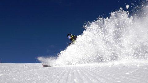 Slow motion - Low angle view of alpine skier spraying snow into camera
