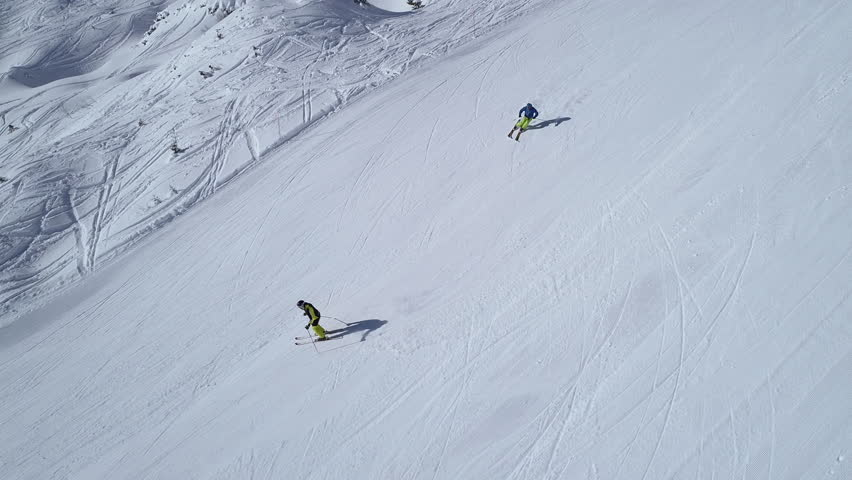 Aerial - Side view tracking shot of good alpine skier skiing down the wide ski slope alone at first. At the end of clip faster skier comes behind and gets dangerously close to first skier | Shutterstock HD Video #34899331