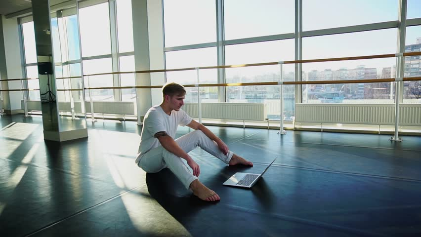 Young male person learning new movements with tutorial using laptop. Male person sitting in white shirt and pants. Concept of Internet sources for self improvement | Shutterstock HD Video #34914331