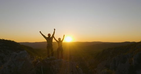 Aerial flight forward - Friends reaching the top and celebrating together at sunset.