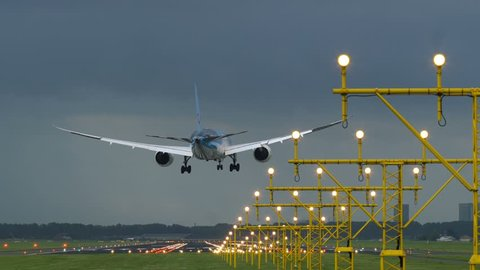 AMSTERDAM, NETHERLANDS - JULY 28, 2017: Boeing 737 of Tui Fly airlines land on with strong side wind at Schiphol airport. Landing lights at foreground. View from the beginning of runway.