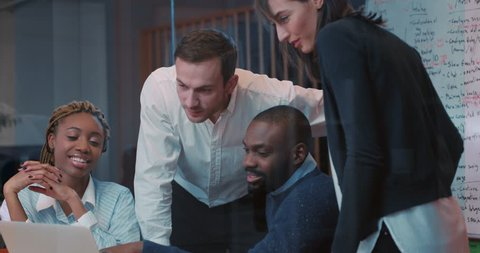 Four employees of prestigious international firm discussing about future deal. Beautiful young African girl suggesting to make some important terms in contract. Close-up. Evening.