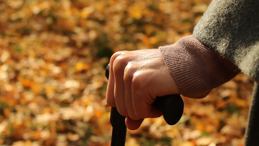 Old granny, using cane to stand, having rest, pause. Autumn background.