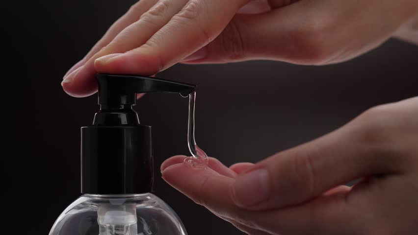 Woman push dispenser and liquid soap squeezed out to hand, closeup shot against black background. Lady washing up hands at bathroom, using soft gel for advanced skin care #34968961