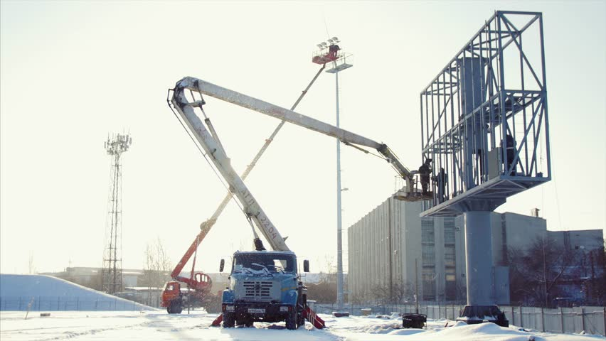 Worker in lift bucket during installation big billboard in bad weather. Workers install a Billboard. Workers and lift