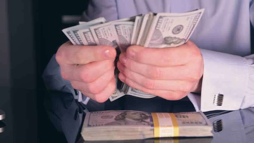 Investing Returns. Online Stock Trader Counting American Dollars on the modern Glassy Desk. | Shutterstock HD Video #35018755