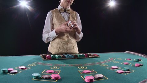 Casino croupier woman shuffles the poker cards and performing trick with cards. Black background. Bright light. Slow motion