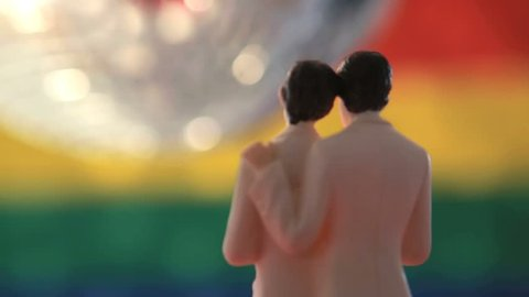Gay groom cake toppers revolving with disco ball in front of gay pride flag