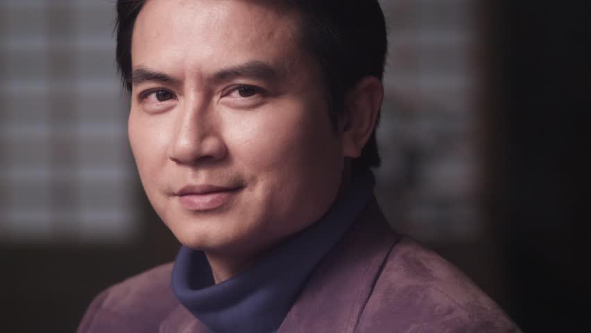 Chinese man turns to camera slow motion closeup