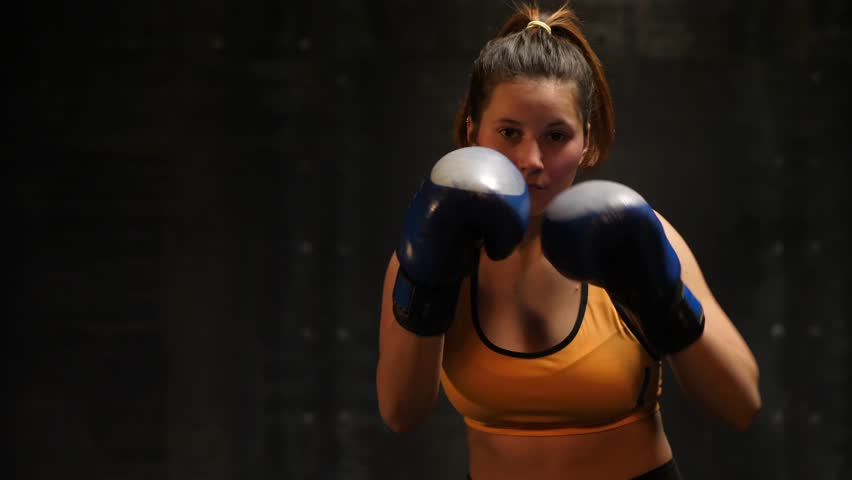 Strong woman fighter martial arts training punches with hands on boxing gloves in air in fighting club | Shutterstock HD Video #35040061
