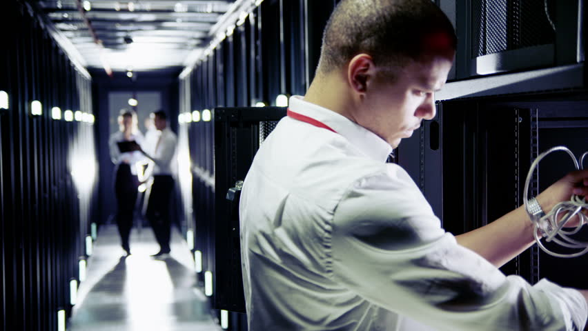 Three people of mixed ethnicity are working in a data center with rows of server racks and super computers. They are walking up and down and checking all of the equipment.  #3510971