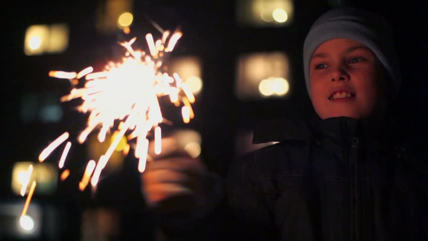 Cheerful boy holds Bengal fire in hand near house at winter night