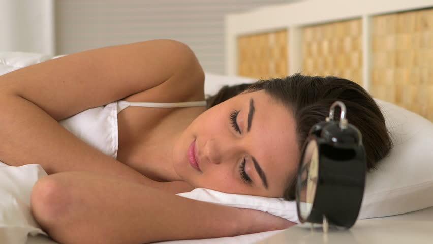 Woman waking up to alarm clock