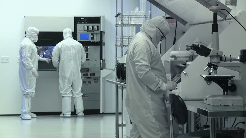 """Clean Room Wide. Scientists / technicians working on silicon chip manufacture in a clean room, wearing full body white """"bunny suit"""" coveralls to avoid contamination.  Wide view."""