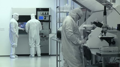 "Clean Room Wide. Scientists / technicians working on silicon chip manufacture in a clean room, wearing full body white ""bunny suit"" coveralls to avoid contamination.  Wide view."
