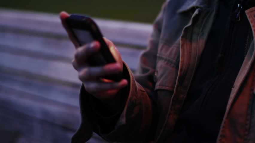 Smartphone User At Night.  Young man illuminated by his smartphone as he uses it