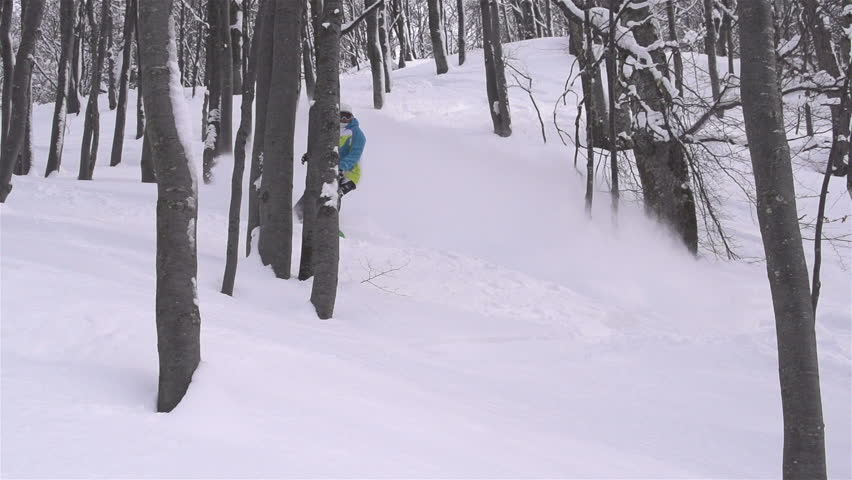 SLOW MOTION: snowboarder doing powder turn in forest