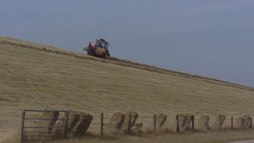 Farmer haying at sea dike, square bales rolling down. The Hondsbossche and Pettemer Zeewering  is a 5,5 km long sea dike in The Netherlands.