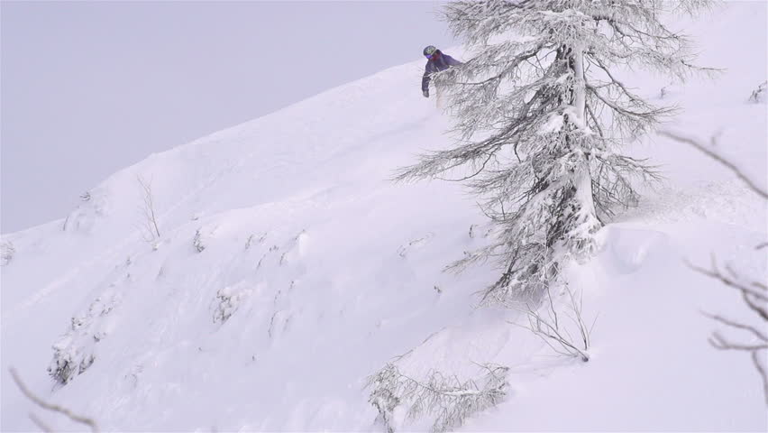 SLOW MOTION: snowboarder jumping over a cliff