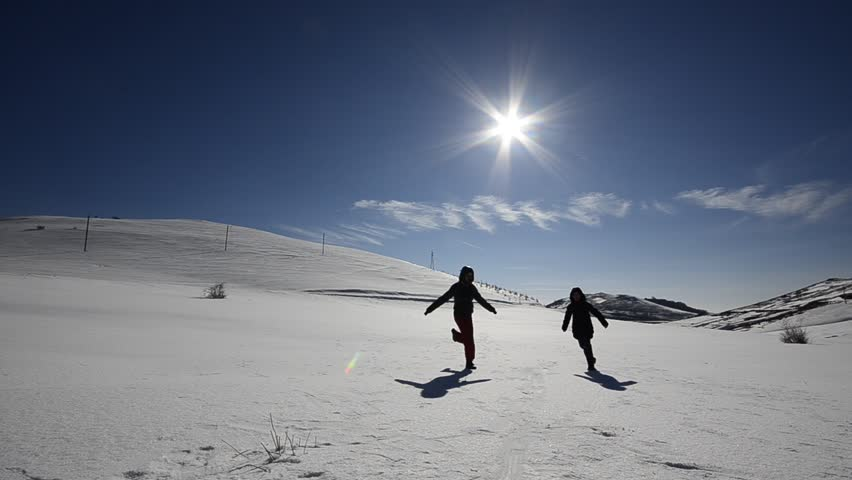 Two kids boy and girl enjoying play run on snow slope. Girl runs toward camera, boy cross sister trail laughing and having fun and joy.