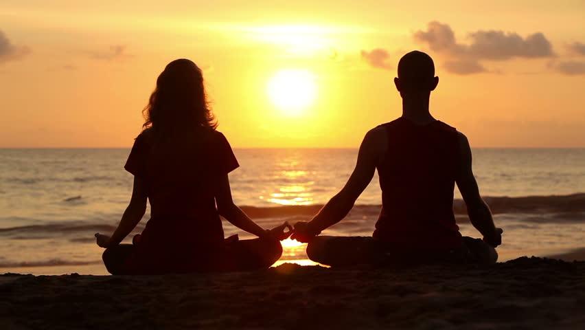 Couple sitting yoga on beach while sunset