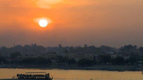 Sunset over Nile river reflecting a golden sky Luxor in Egypt.
