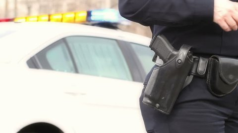 Law enforcement police officer draws her gun, with police car lights in the background . HD 1080p.